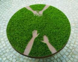 HANS-OISEAU >Gespräch am runden Tisch, oder:.. Ein-Griffe< 1989 Tischobjekt: Tränenblech, Erde, Weizen 85 x 162cm Ø Besitz des Künstlers